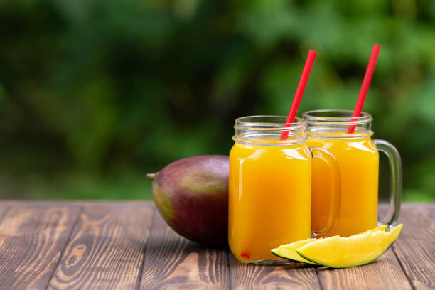 jugo de mango en tarros de albañil - foto de stock