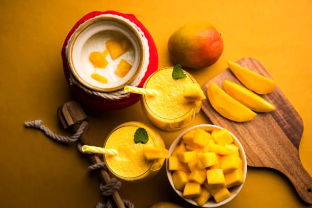 Mango-Lassi oder Smoothie in großen Gläsern mit Quark, geschnittenen Fruchtstückchen und blender – Foto