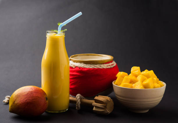 Mango-Lassi oder Smoothie in kleinen Flaschen mit Quark, geschnittenen Fruchtstückchen und Blender. Stimmungsvollen Hintergrund, selektiven Fokus – Foto