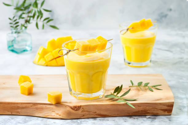Mango Lassi, yogurt or smoothie with turmeric. Healthy probiotic Indian cold summer drink Mango Lassi, yogurt or smoothie with turmeric. Healthy probiotic Indian cold summer drink mango stock pictures, royalty-free photos & images