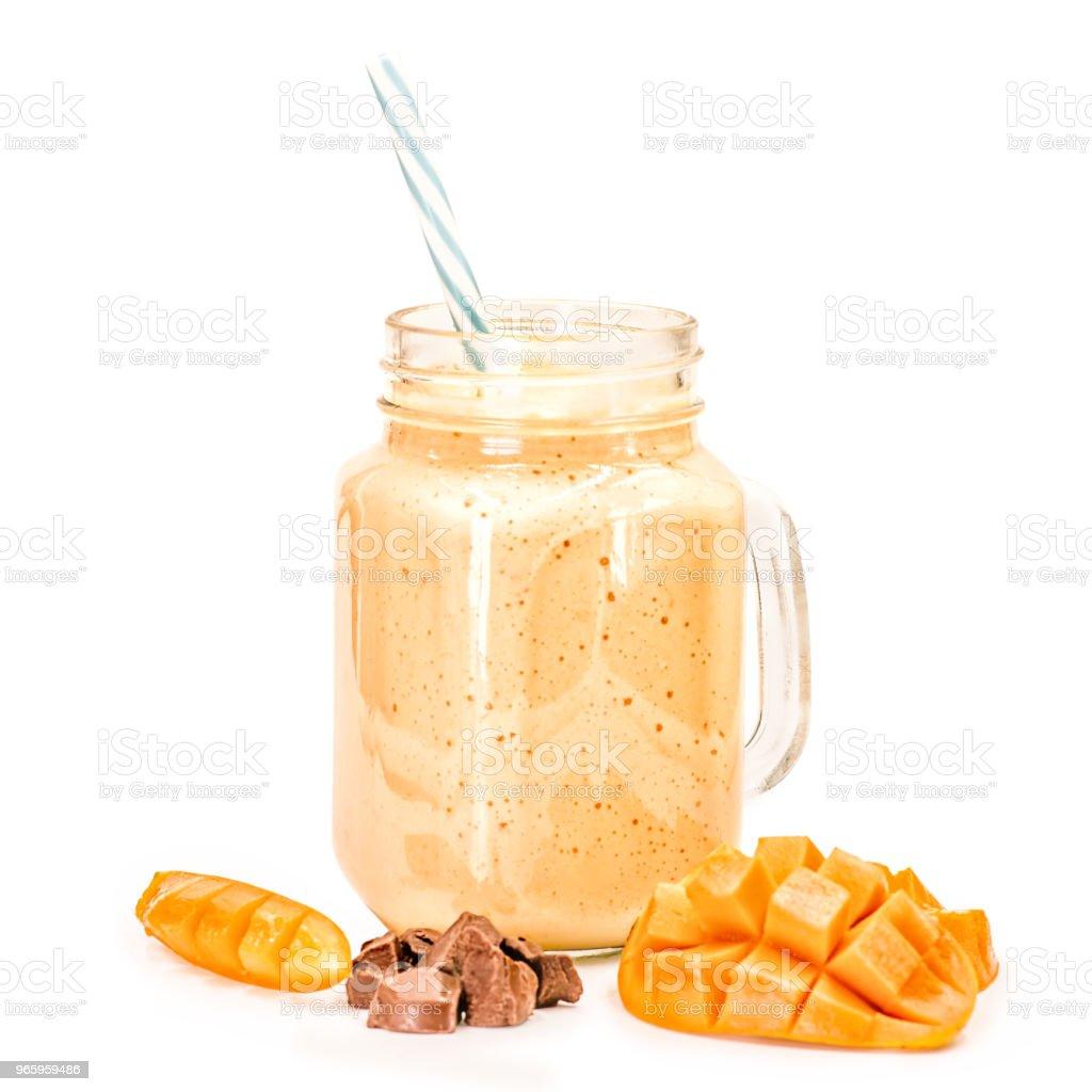 Mango milkshake in mason jar met blauw en wit stro drinken versierd met mango segmenten en chocoladestukjes geïsoleerd op witte achtergrond - Royalty-free Activiteit - Bewegen Stockfoto
