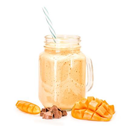 Mango Milkshake In Mason Jar Met Blauw En Wit Stro Drinken Versierd Met Mango Segmenten En Chocoladestukjes Geïsoleerd Op Witte Achtergrond Stockfoto en meer beelden van Activiteit - Bewegen