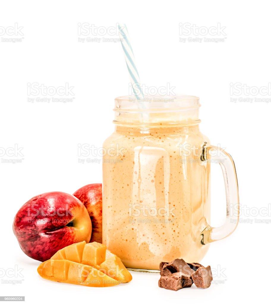 Mango Milchshake im Einmachglas mit blauen und weißen trinken Stroh dekoriert mit Mango Stück, zwei Nektarinen und Schokolade isoliert auf weißem Hintergrund - Lizenzfrei Bewegungsaktivität Stock-Foto