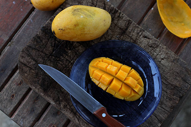 Mango on old wooden chopping board stock photo