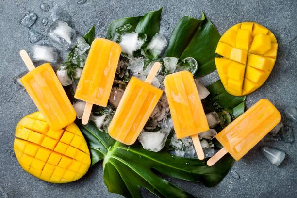 mango eis am stiel über grüne tropische palmblatt auf grauem stein hintergrund. overhead, ansicht von oben - mango eis am stiel stock-fotos und bilder