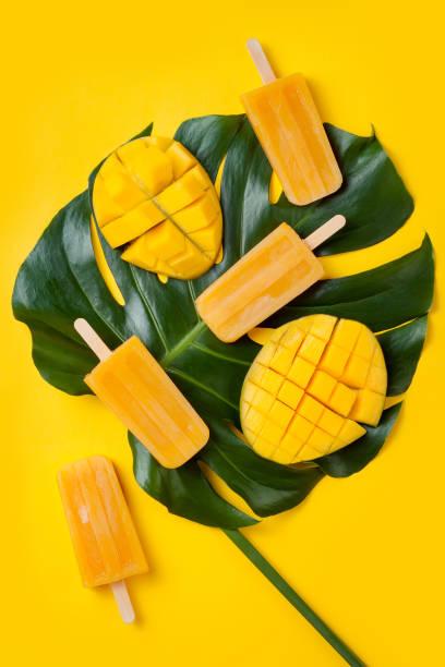 mango eis am stiel über grüne tropische palmblatt auf gelben farbigen hintergrund. minimalstil flach legen. overhead, ansicht von oben - mango eis am stiel stock-fotos und bilder