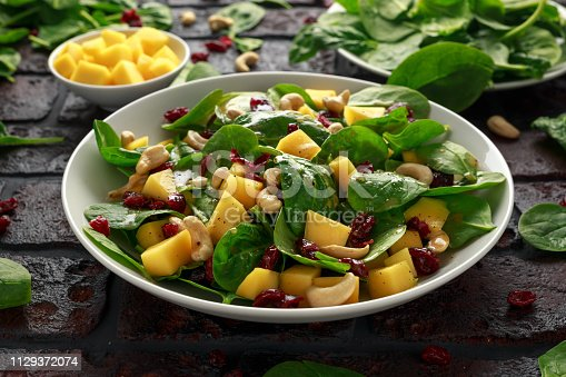 Mango Spinach salad with dried cranberries and nuts. healthy food