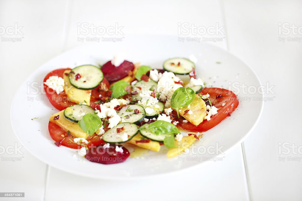 Mango, tomato, beetroot and cucumber salad with fresh cheese royalty-free stock photo
