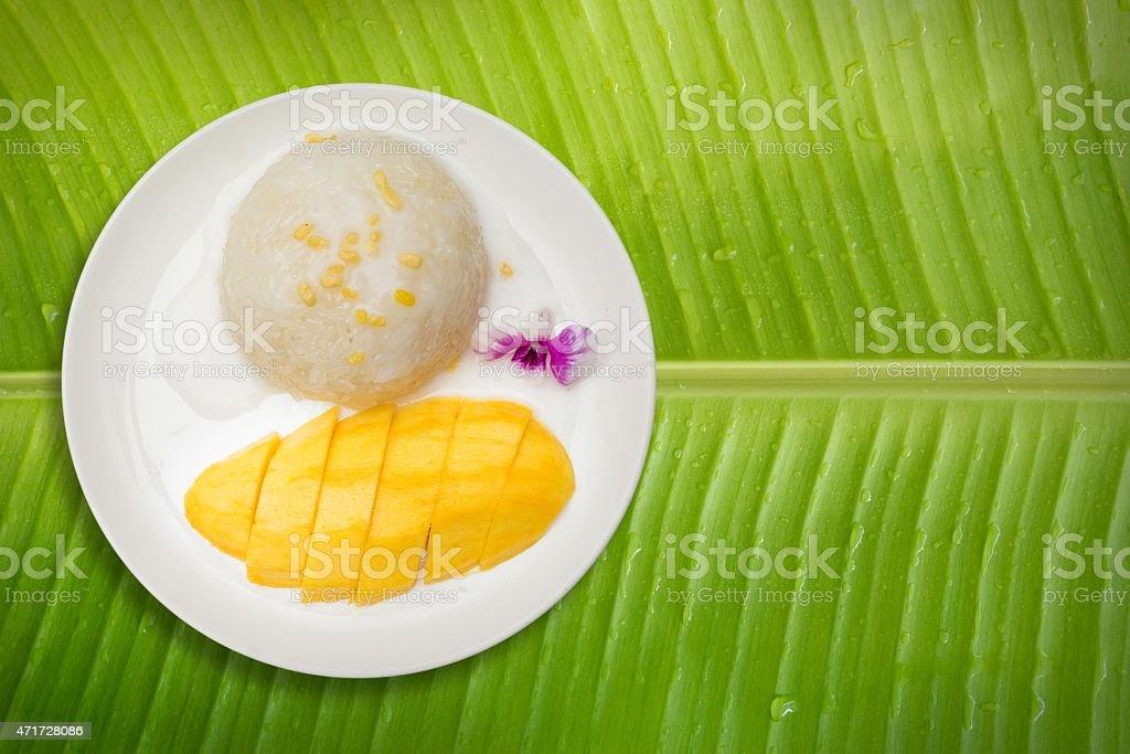 Mango with Sticky Rice on banana leaf background stock photo