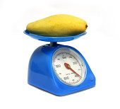 blue color Scales and yellow mangoes on white background