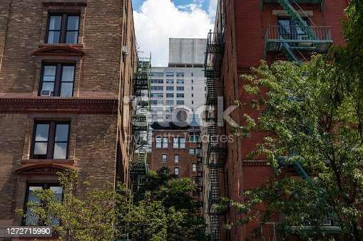 A Manhattan alley with old brick skyscrapers with fire escapes looking towards a building with an old water tower on the Upper West Side of New York City