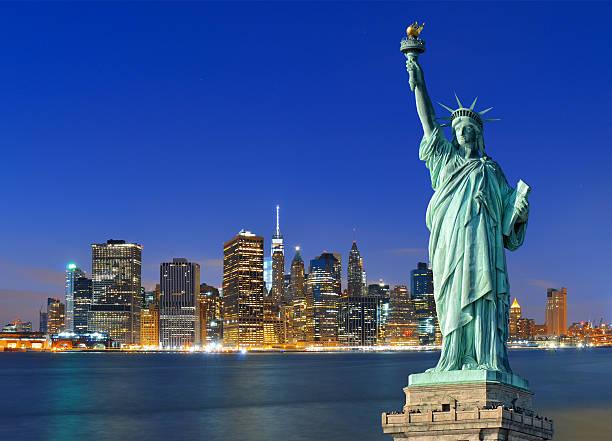 manhattan de nuit et de la statue de de la liberté. - new york photos et images de collection