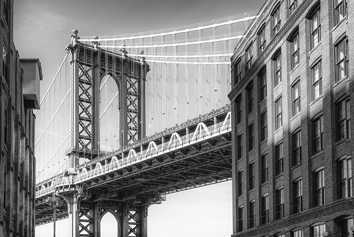 A black and white image of Manhattan Bridge as seen from Washington Street in the Dumbo district of New York City.