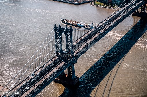 Aerial view of a Manhattan Bridge in New York with a small vessel passing below it.