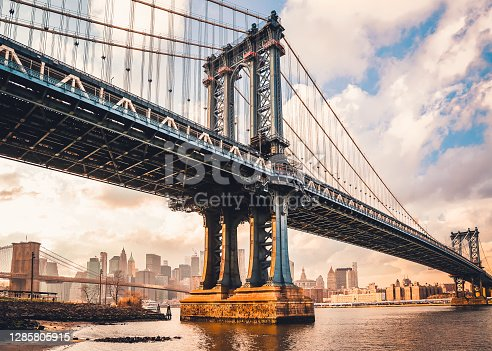 Manhattan Bridge over East River at sunset in New York City, USA. Beautiful skyline with skyscrapers. Panoramic view from Brooklyn waterfront. Urban perspective.