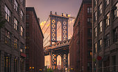 Manhattan bridge seen from a brick buildings in Brooklyn street in perspective, New York, USA. Shot in the evening