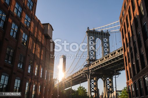 The Manhattan bridge from Brooklyn with the sun hitting One Manhattan Square building.