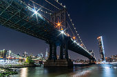 An evening view of the Manhattan Bridge with the Brooklyn Bridge and Manhattan Skyline in the background