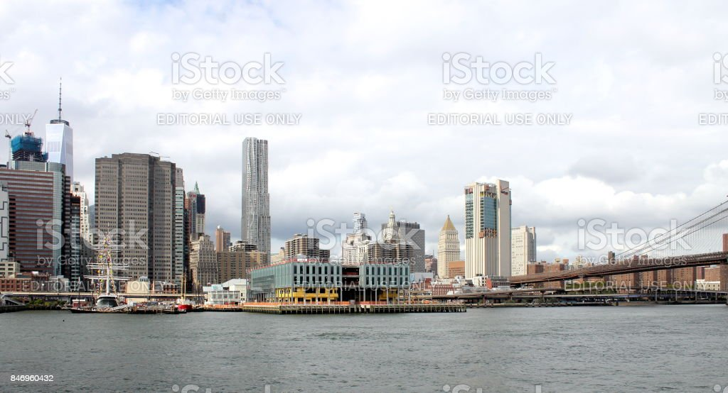 Manhattan buildings lining the East River with the Brooklyn Bridge to the right. stock photo