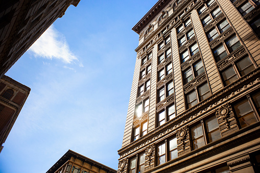 A pedestrian's perspective of buildings and sky in downtown New York City.