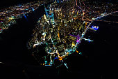 Aerial view of the Empire State Building taken from a helicopter above New York at night time. East River and the Two Bridges are also visible.