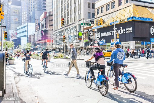 istock Manhattan NYC buildings of midtown Times Square, Broadway avenue road, signs for Duane Reade, taxi cab, people riding bicycles bikes citibike on 50th street 913065712