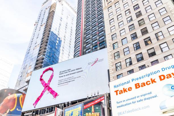 manhattan nyc gebäude von midtown, times square, broadway avenue road, zeichen anzeigen für pink ribbon brustkrebskampagne, dea, nationale verschreibungspflichtiges medikament - bandanzeige stock-fotos und bilder