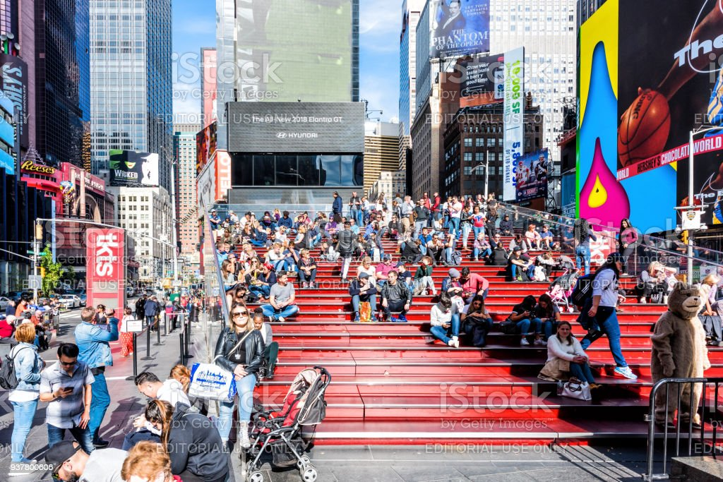 Manhattan NYC buildings of midtown Times Square, Broadway avenue road, Duffy Square with many crowd people sitting on benches bleachers stairs stock photo