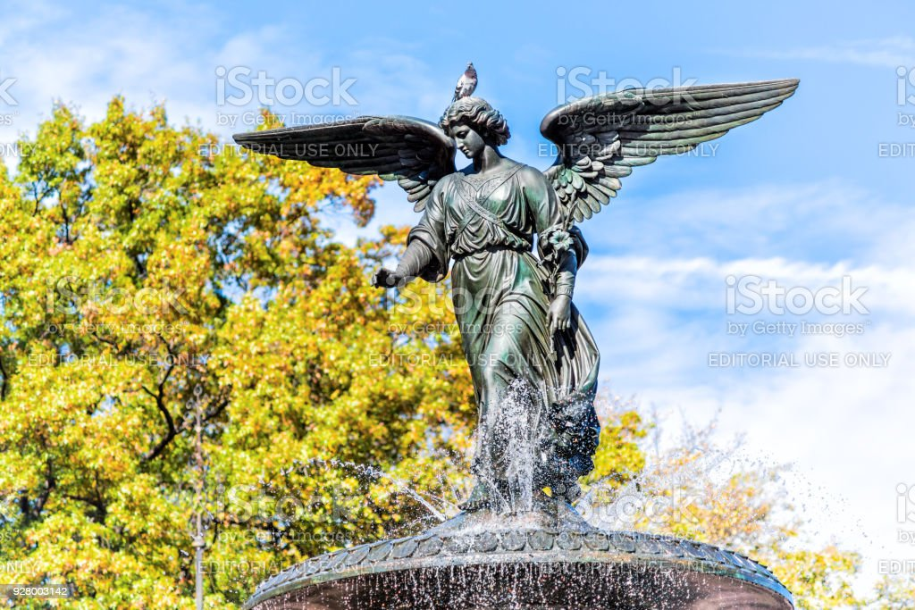 Manhattan NYC Central park at Bethesda Arcade terrace by fountain, nobody, closeup of angel statue, pigeon bird on sunny day stock photo