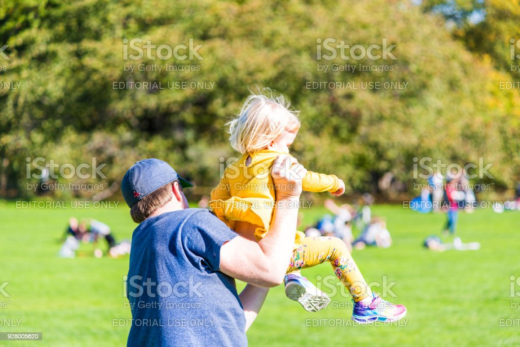 Manhattan NYC Central park Great Lawn in with young children girls toddlers running playing having fun on green grass meadow with dad father stock photo