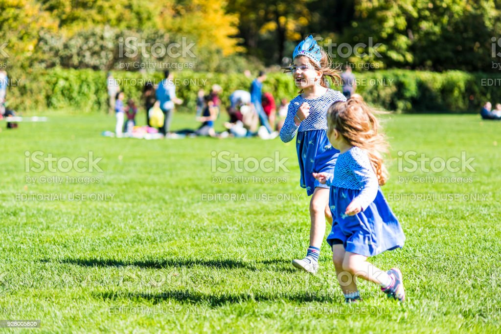 Manhattan NYC Central park Great Lawn in with young children girls toddlers running playing having fun on green grass meadow stock photo