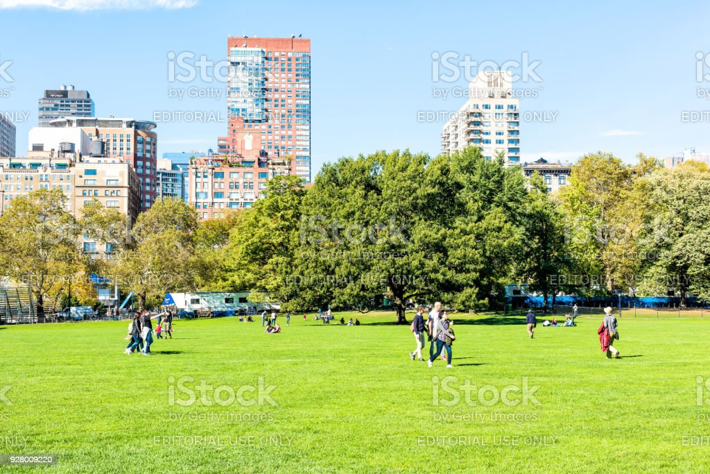 Manhattan NYC Central park Great Lawn with people walking on green grass meadow in autumn fall season, buildings cityscape skyline stock photo
