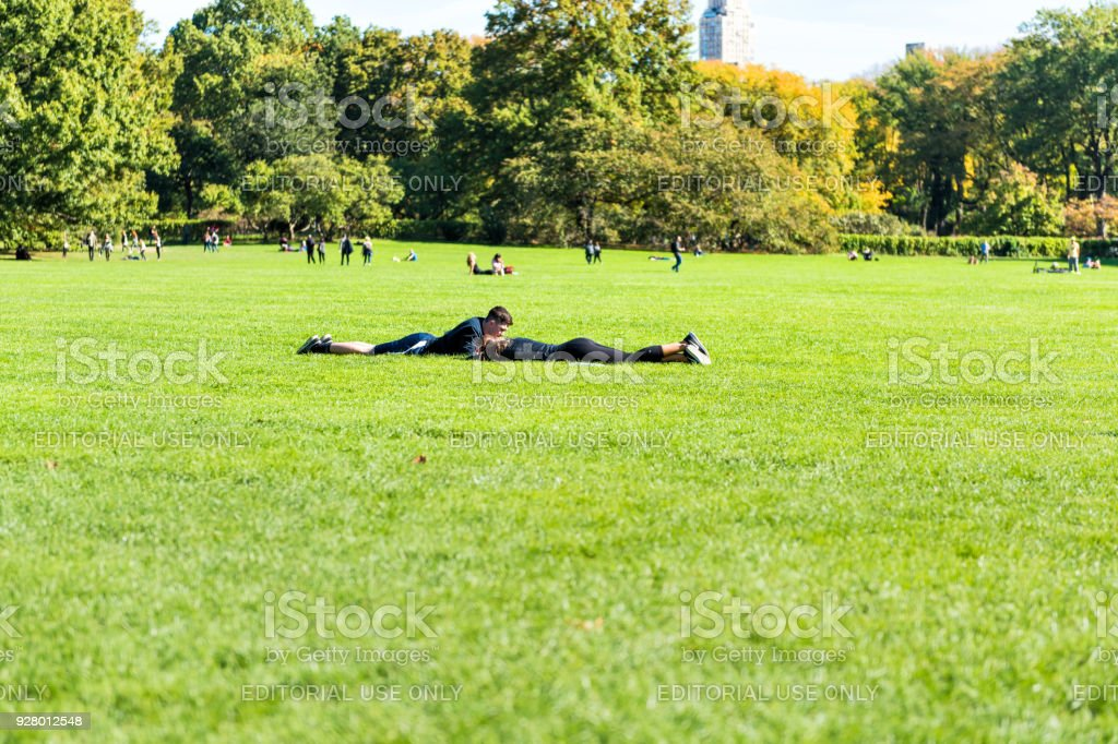 Manhattan NYC Central park with couple people lying down having picnic on great lawn grass meadow in autumn fall season stock photo