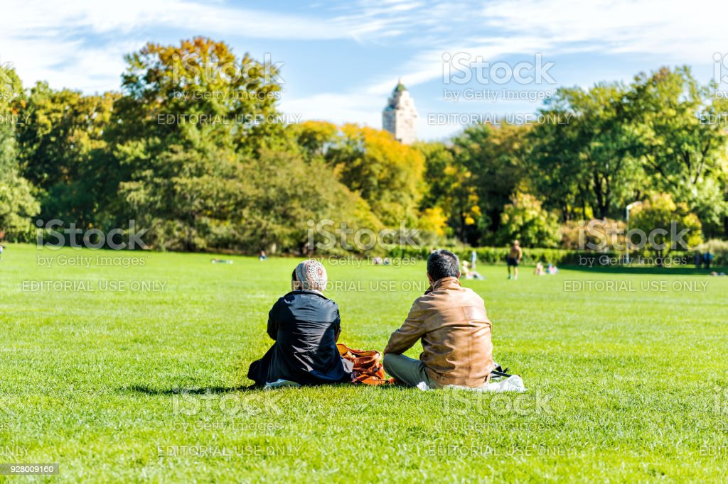 Manhattan NYC Central park with couple people sitting having picnic in front of buildings skyscrapers view on great lawn grass meadow in autumn fall season stock photo