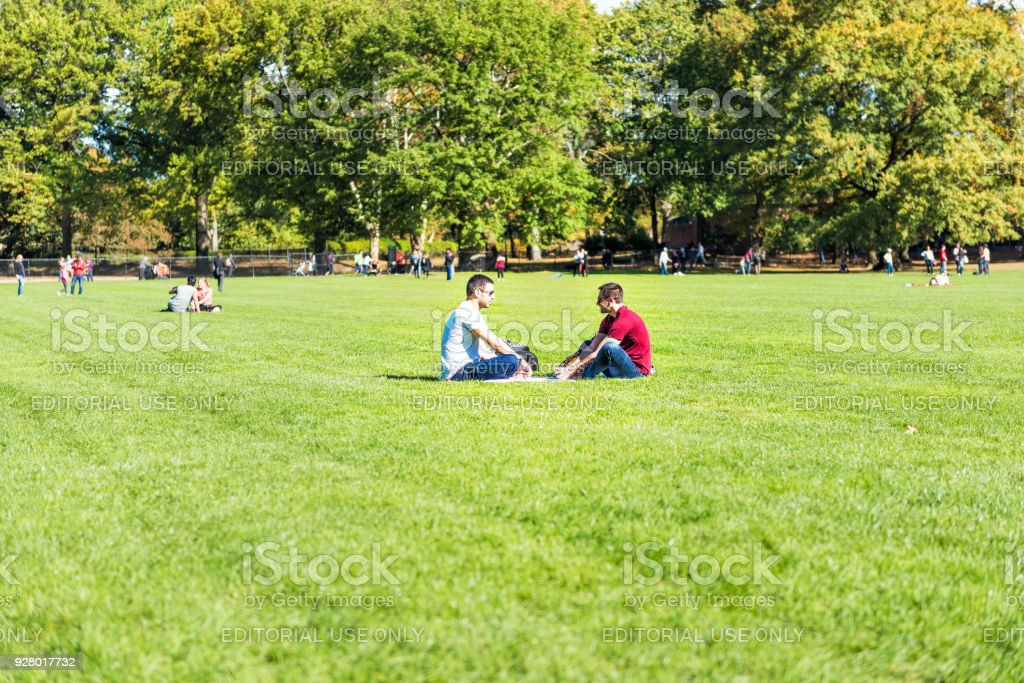 Manhattan NYC Central park with couple people sitting having picnic on great lawn grass meadow in autumn fall season stock photo