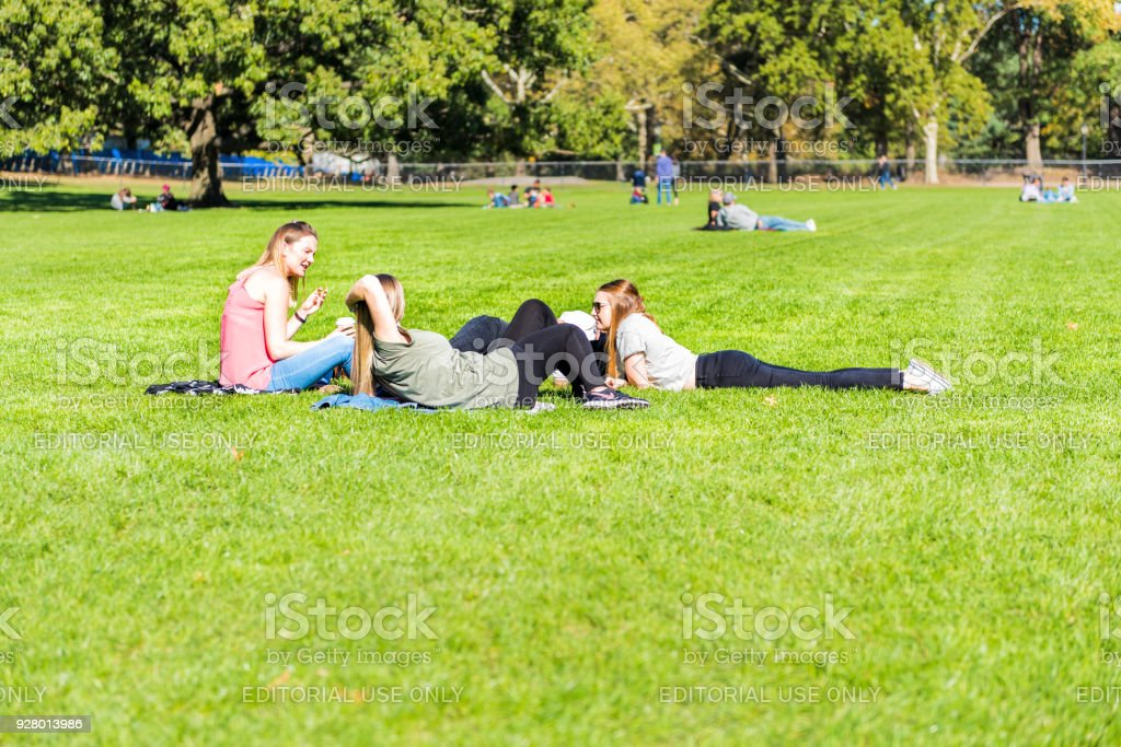 Manhattan NYC Central park with girls women friends happy picnic talking on great lawn grass meadow in autumn fall season stock photo