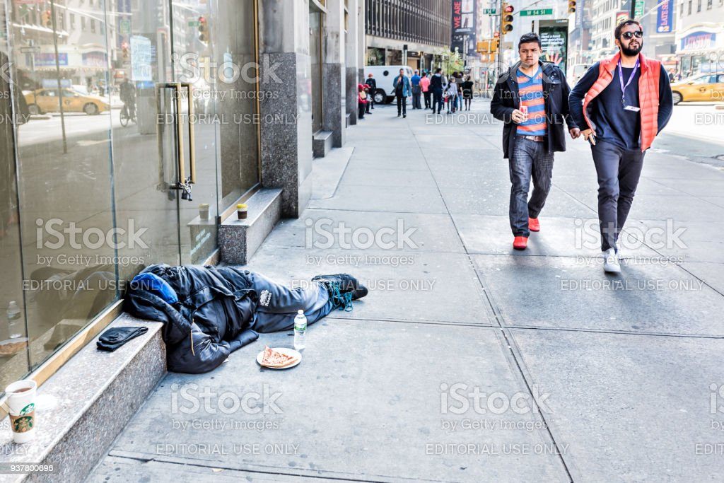Manhattan NYC sidewalk in midtown Times Square, Broadway street avenue road, homeless man sleeping, people walking by stock photo