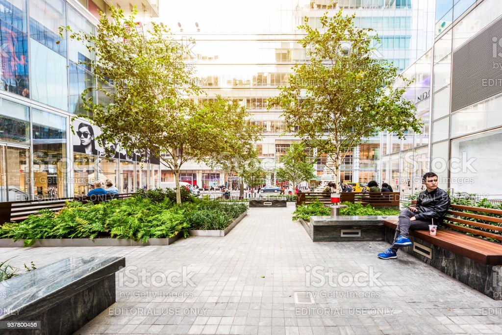 Manhattan NYC Verizon Plaza green urban park, buildings of midtown by Times Square, road, people street outside, charging hub stock photo