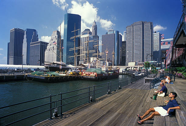 Manhattan New York City,NY,USA-August 29,1999:Some Manhattan office buildings from South Street Seaport.Radio listener,puzzle solver and sun bathing people on Pier 17 in August,1999.Great place for enjoying a sunny day. south street seaport stock pictures, royalty-free photos & images