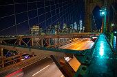 Manhattan skyline at night seen from the illuminated beautiful Brooklyn bridge. New York City, USA.