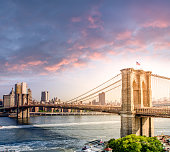 A square composition of the New York City skyline at sunset with a dramatic cloudscape and the historic Brooklyn Bridge in the foreground.