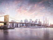 A square composition of the New York City skyline at sunset with a dramatic cloudscape and the historic Brooklyn Bridge in the foreground. A long exposure to give the water a smooth effect.
