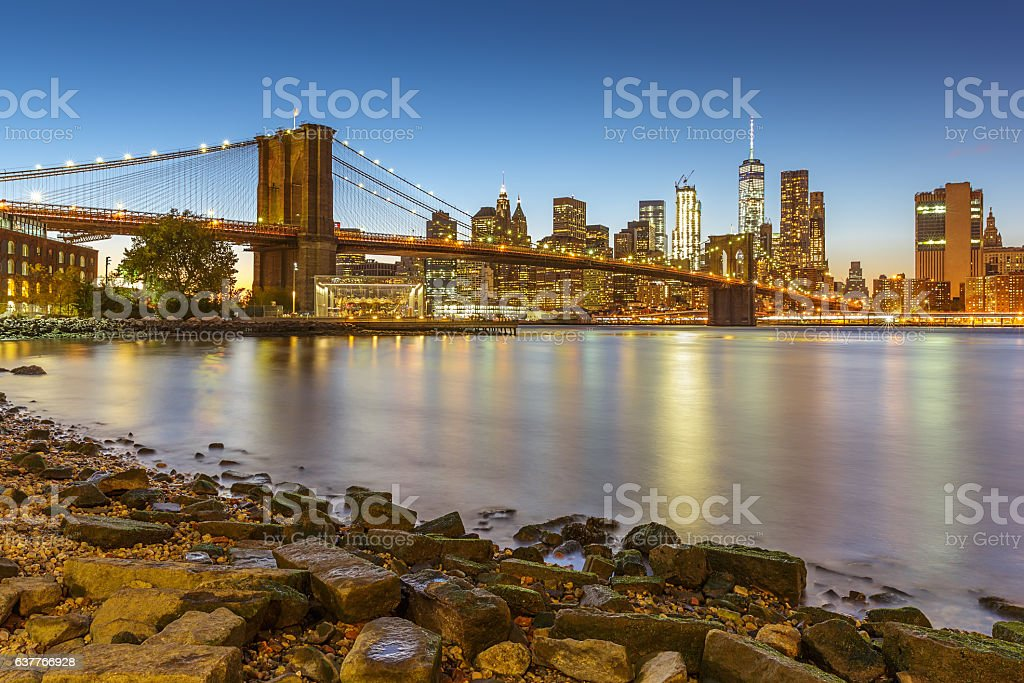 Manhattan skyline at sunset with Brooklyn Bridge stock photo