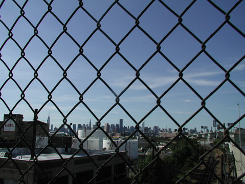 Long Island City, NY, USA - September 6, 2003: View of the Manhattan skyline as seen through the chain link fence guard on the John Jay Byrne Bridge in Queens. Lukoil ad visible. Train tracks below.