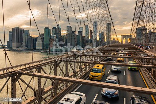 Traffic on Brooklyn Bridge at sunset with Manhattan skyline in the background (New York, USA)