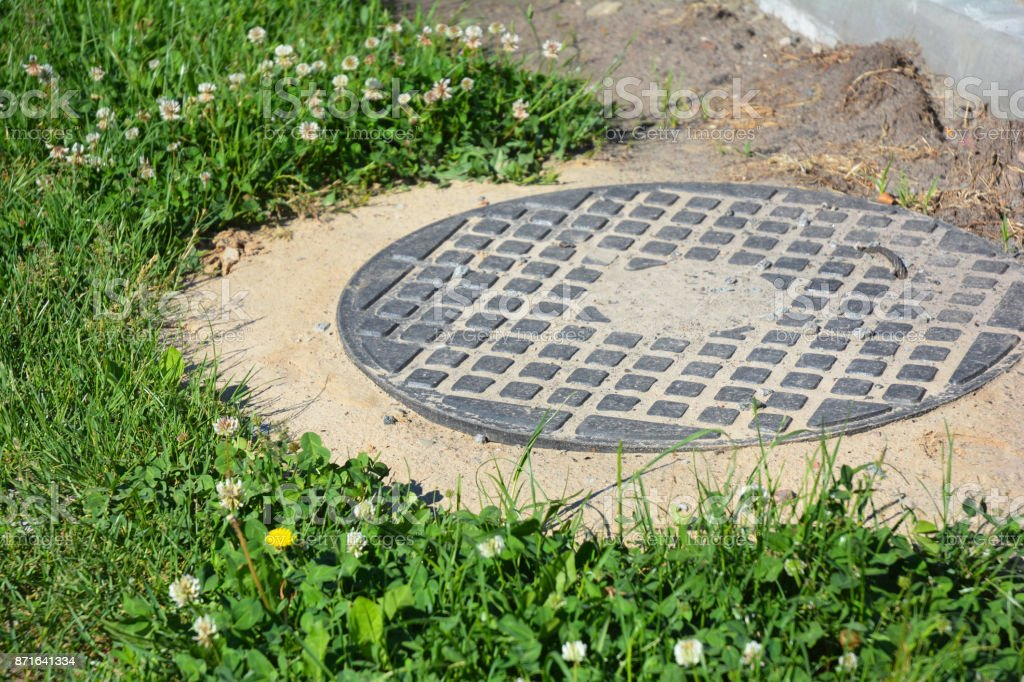Beau Manhole Cover Installation In The Garden. Royalty Free Stock Photo