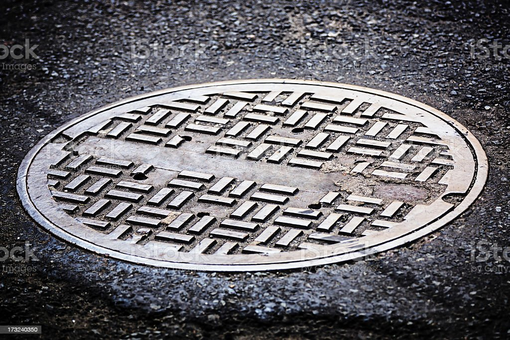 Manhole cover on street stock photo