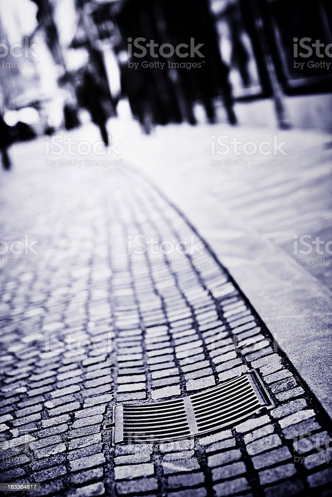 Manhole cover on wet street paved with granite setts royalty-free stock photo
