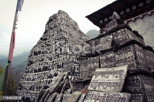 Mani Stones of Buddhism with six syllabled mantra Om Mani Padme Hum (means-Praise to the Jewel in Lotus) near Phakding village in Khumbu valley on the way to Everest base camp, Solukhumbu, Nepal.