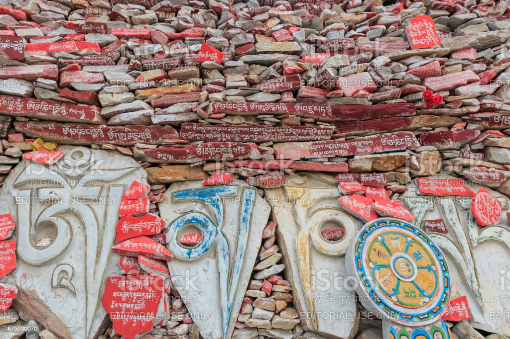 Mani stones wall at the Mani Temple (Mani Shicheng) wall with buddhist mantra Om Mani Padme Hum engraved in Tibetan in Yushu, China stock photo